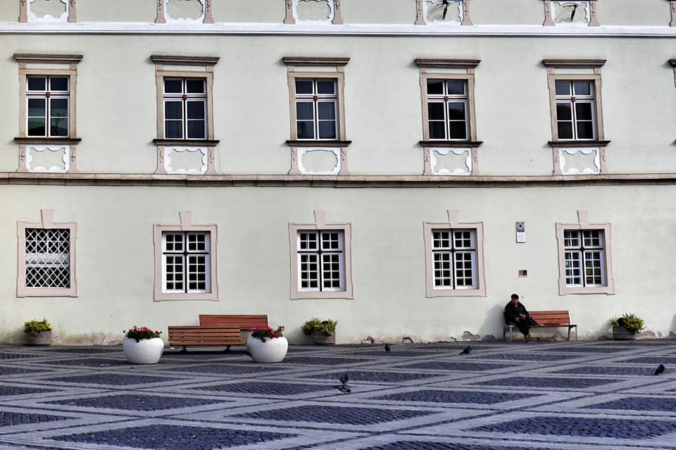Man sitting alone on a park bench in empty Piata Mare - Sibiu, Romania
