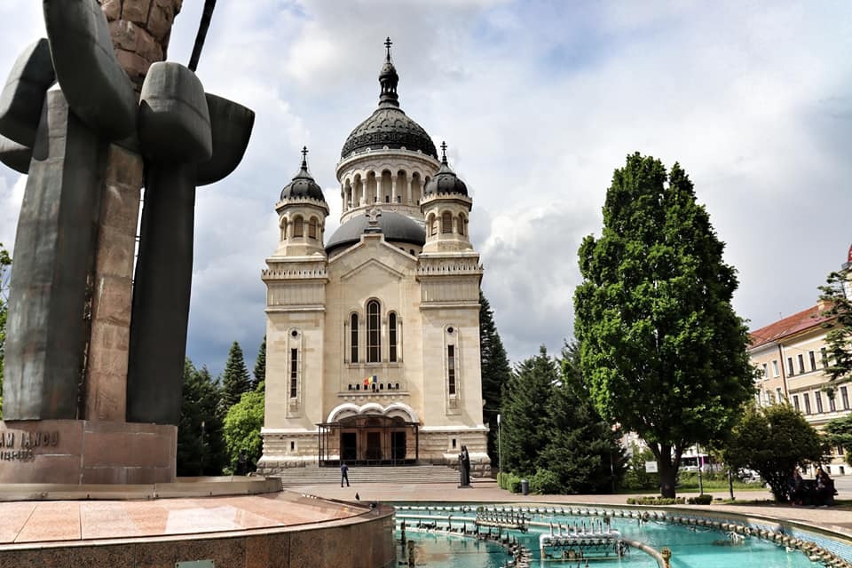 Orthodox Cathedral in Cluj with black onion domes and a pale cream facade with a turquoise fountain in the foreground.