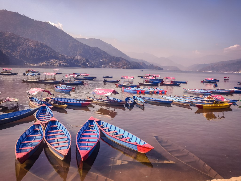Colorful blue and red boats sit on a river under hazy skies in Pokhara, Nepal.  The Himalaya mountains are seen in the background.
