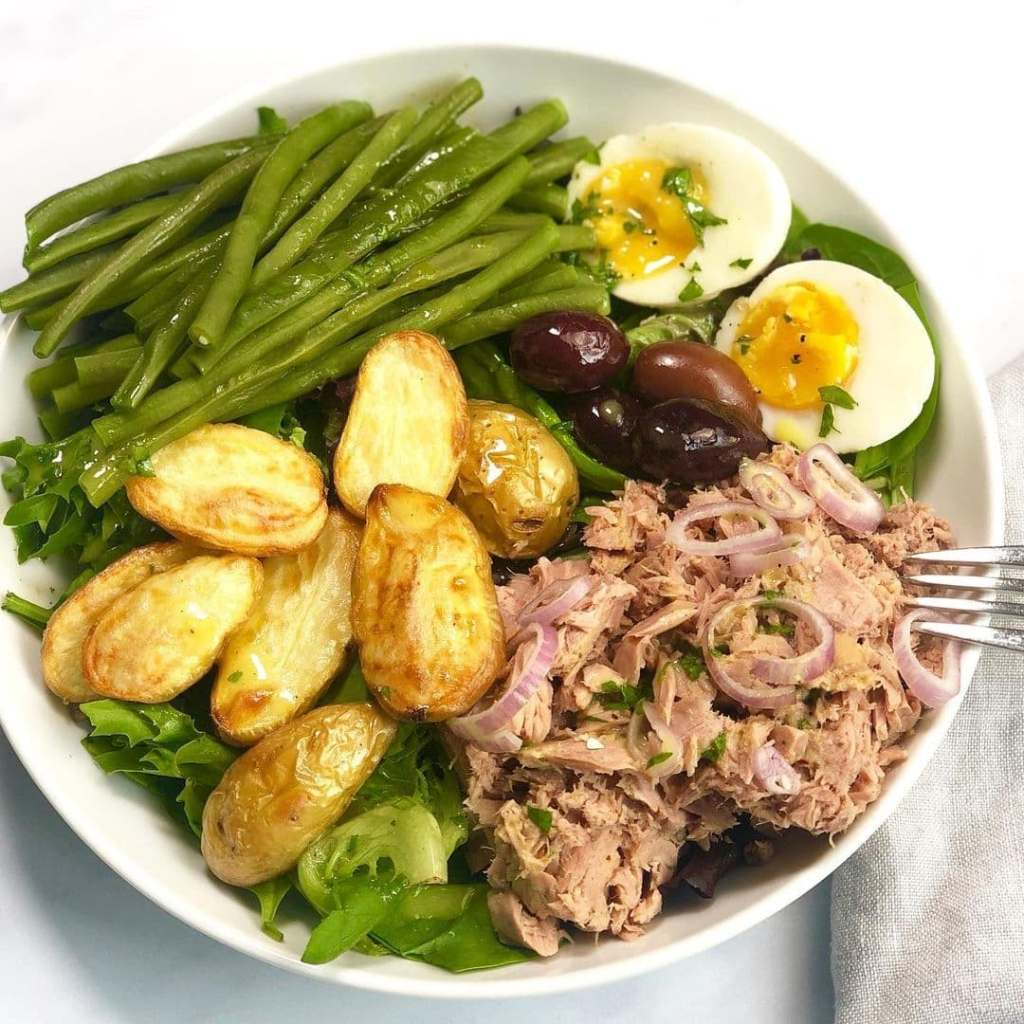 Composed salad of green beans, potatoes, eggs, olives, and tuna - salade nicoise, a traditional French salad.