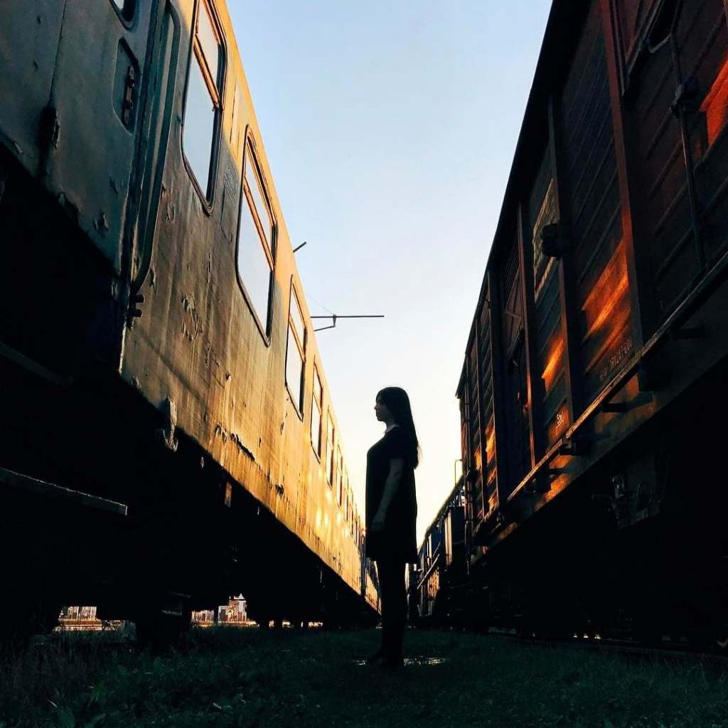 Silhouette of a woman standing in between two old trains in Cluj-Napoca, Romania