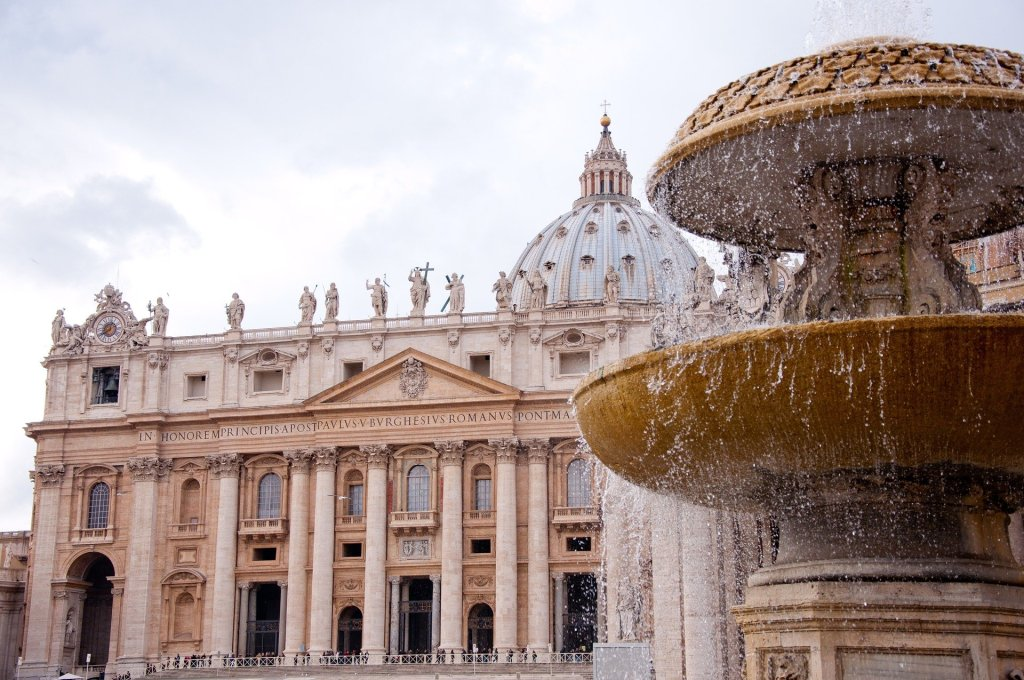 St. Peter's Basilica in background with water splashing out of a fountain in the foreground.