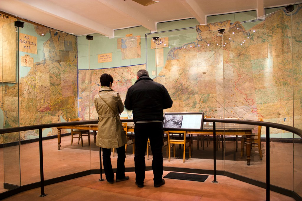 Couple in the Musee de la Reddition looking through the glass into the map room.