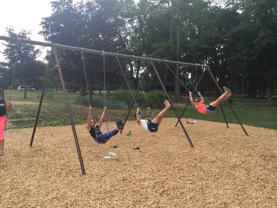 Women swinging on playground swings on break from YTT.