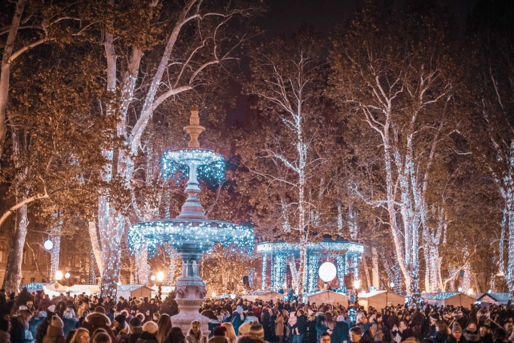 Sparkling lights are hanging from fountains and gazebos in the center of Zagreb's Advent Christmas Market with crowds of people gathering below.