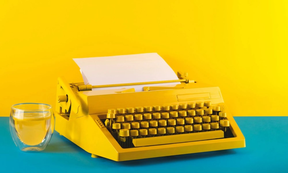 yellow bright typewriter on a yellow and blue background next to glass of water symbol for writing t20 Wgp931 scaled
