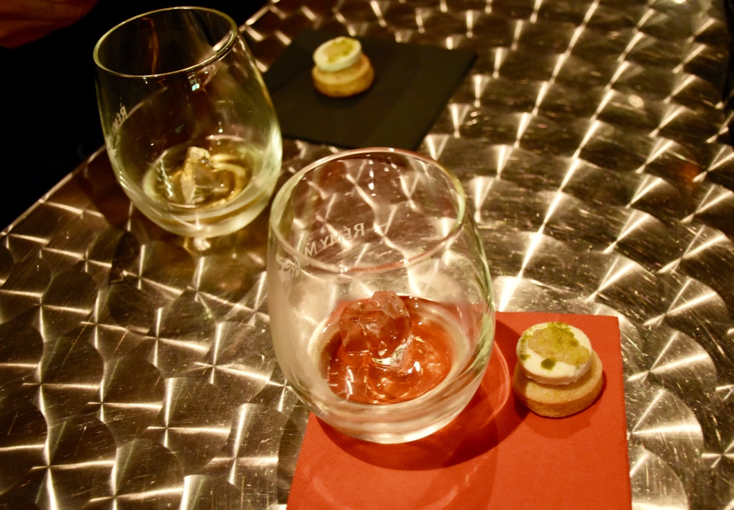 Our cognac glasses and canapes sit on a shiny metal table at the Remy Martin tasting room.