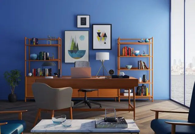 a mid century modern styled office with blue wall behind it.