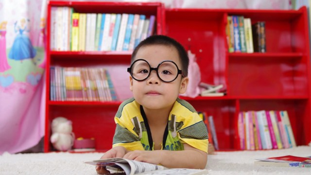 Little boy with glasses on floor reading book in front of organized red bookcase