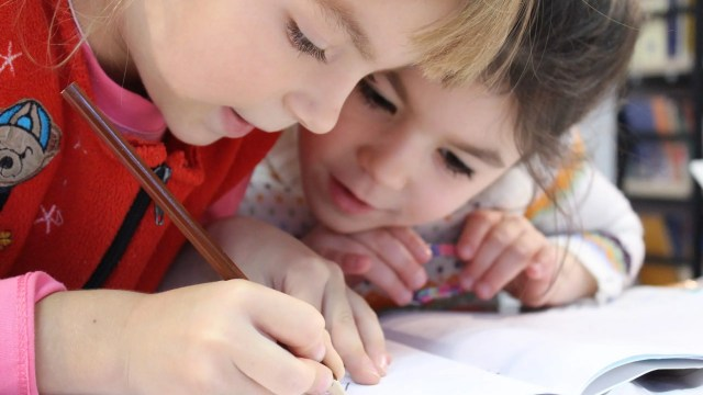 two children looking at the one child writing something on a paper