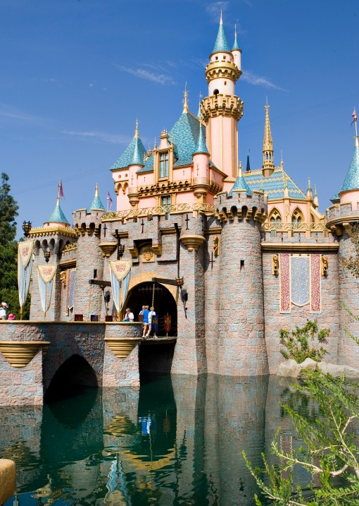"LOVELY LANDMARK -- Sleeping Beauty Castle at Disneyland is the centerpiece of Fantasyland, and one of the most recognizable structures in the world.  Surrounded by beautiful flowers and whimsical topiary, the Disneyland landmark beckons park visitors to explore the different realms of the place ""Where Dreams Come True.""  Walt Disney wanted this castle to be a friendly and welcoming presence in his park so it was built on a smaller scale than its European counterparts."