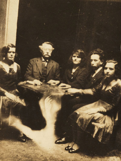 A photograph of a group gathered at a seance, taken by William Hope in about 1920. The information accompanying the spirit album states that the table is levitating. In reality, the image of a ghostly arm has been superimposed over the table using a double exposure.