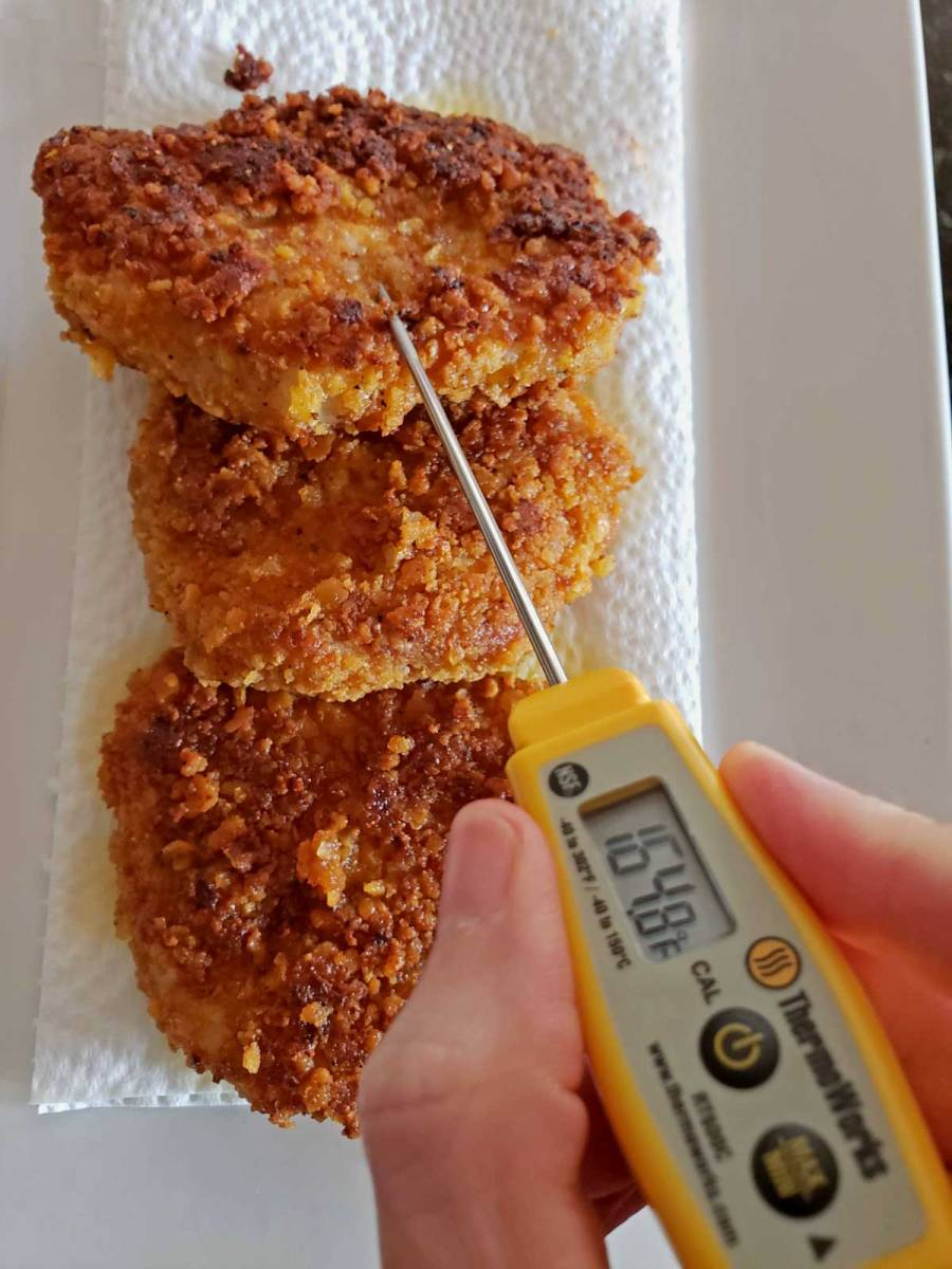 pocket thermometer checking pork chop temperature