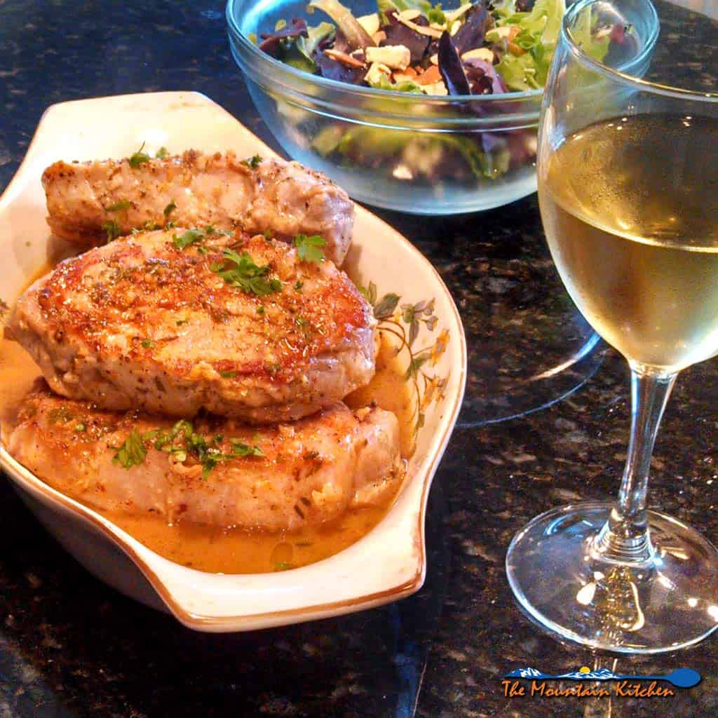 Sexy Pork Chops are smothered in a wonderful zesty sauce made of white wine, chicken broth, and garlic then finished off with lemon and fresh herbs. | TheMountainKitchen.com