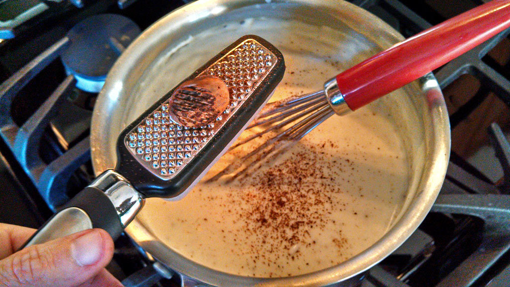 grating nutmeg into bechamel