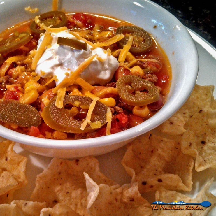 This easy to follow crock-pot Taco Soup is made of ground beef, seasoned with taco spices and cooked with beans and corn in a rich tomato sauce. Yumminess! | TheMountainKitchen.com