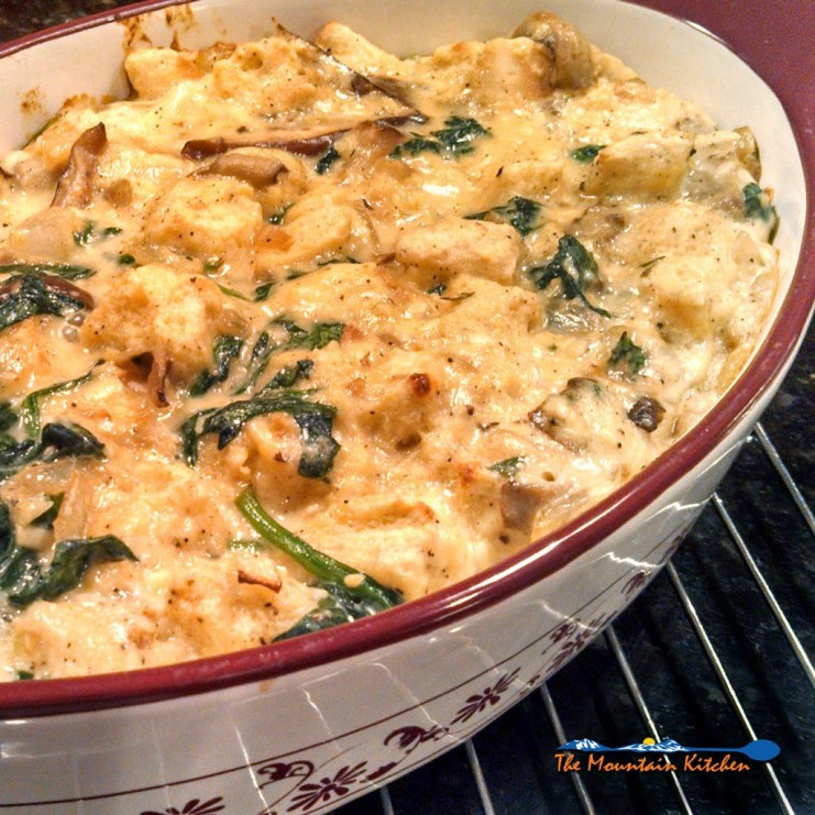 Mushroom spinach strata is a savory bread pudding made of bread, eggs, cheese mushrooms and spinach made with Gouda and Gruyere cheeses. Brunch or dinner! | TheMountainKitchen.com