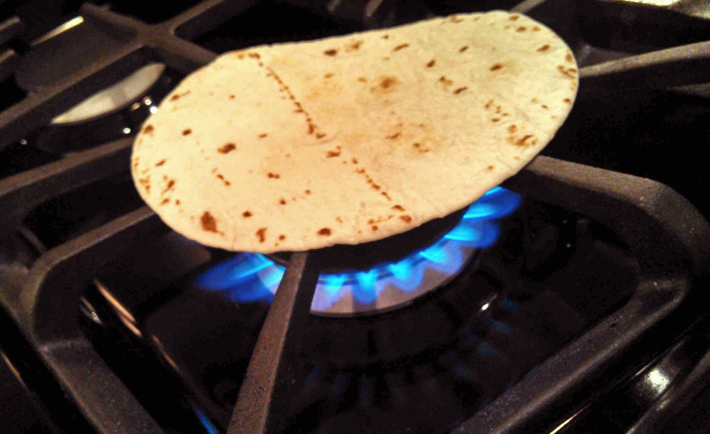 charring tortilla over open flame