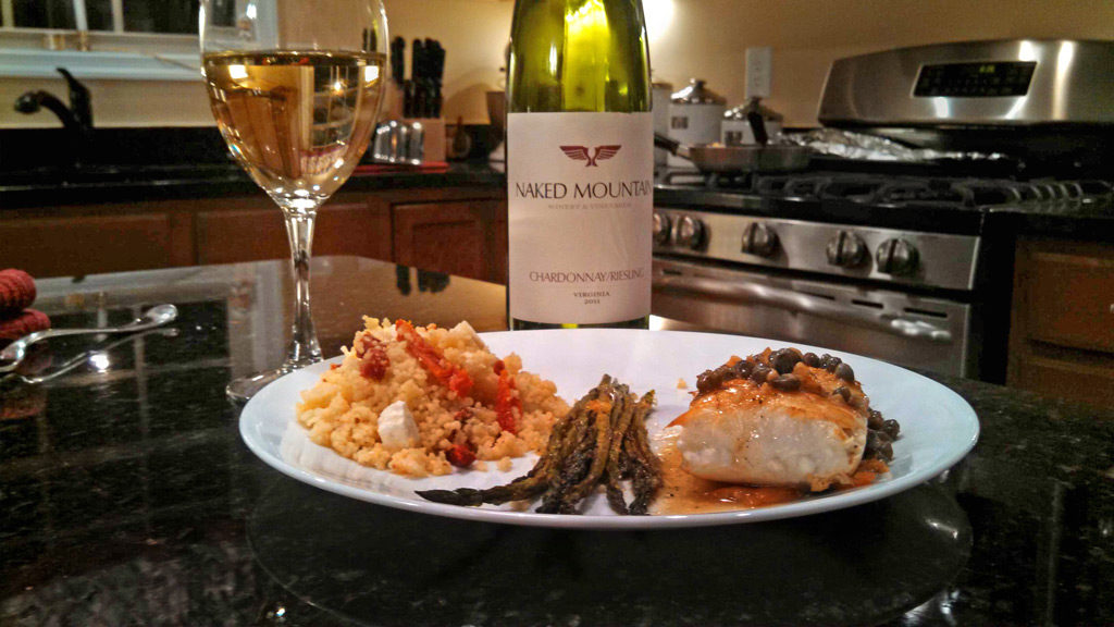 Halibut fillets with a caper butter sauce with sides and wine