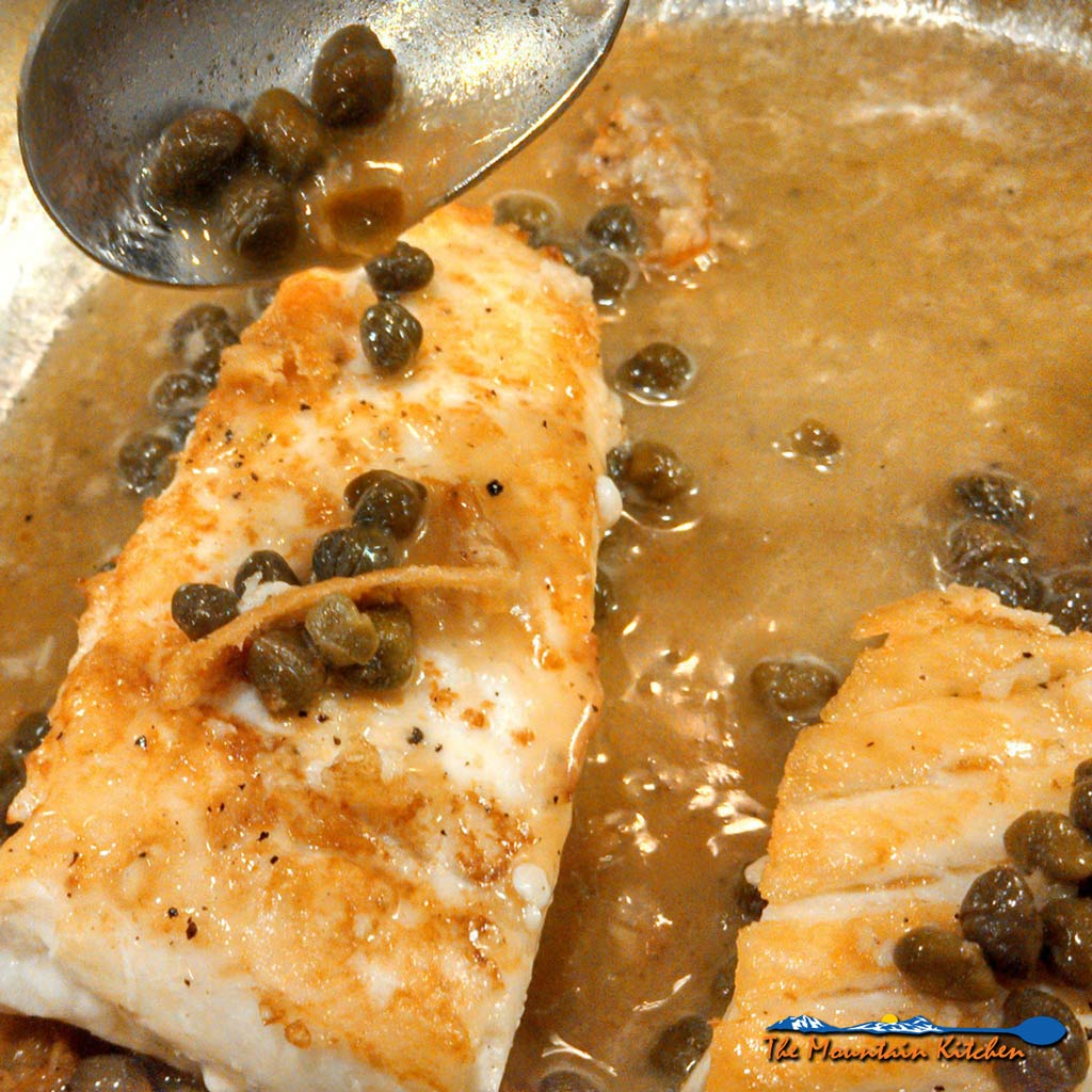 Halibut fillets with a caper butter sauce made of capers, garlic, wine, and butter. Make a romantic meal in just 25 minutes following this easy recipe!