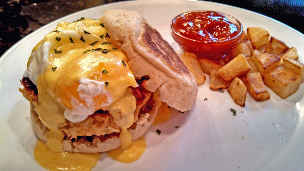 Crab Cakes Eggs Benedict with skillet potatoes on plate