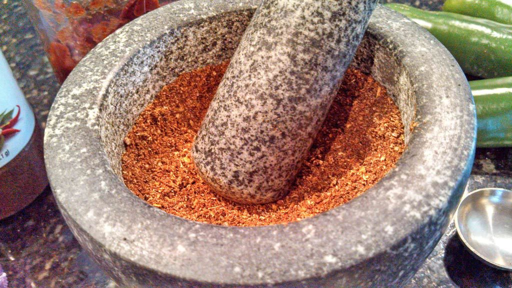 spices ground inside mortar with pestle