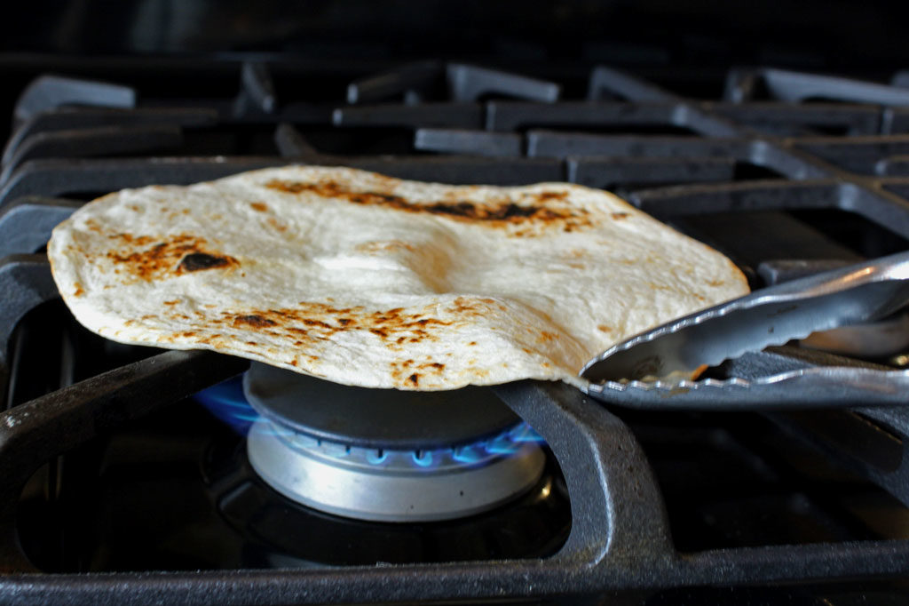 toasting tortilla over gas flame