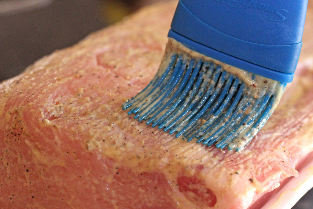 brushing the pork with mustard