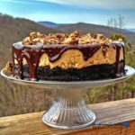 Reese's Peanut Butter Cheesecake on cake plate with mountain view