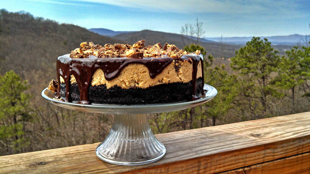 Reese's Peanut Butter Cheesecake on cake stand with mountain view
