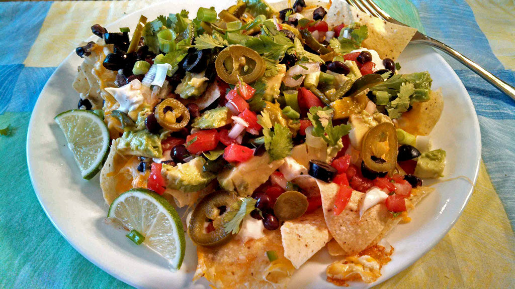 vegetarian nachos on a plate with lime slices