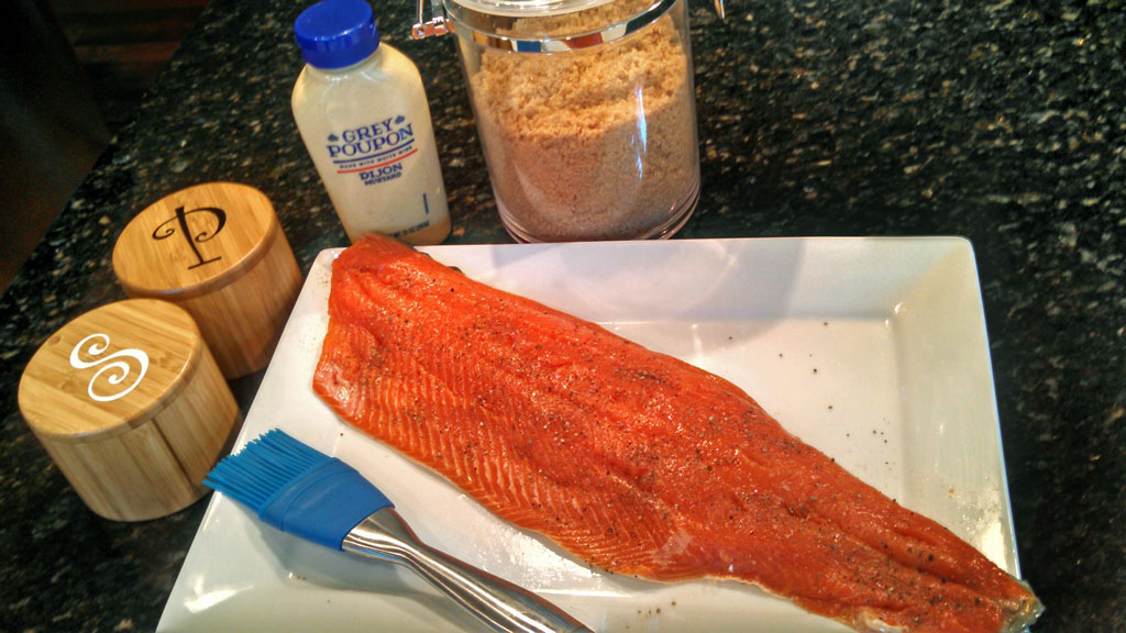 This cedar plank smoked salmon is brushed with a brown sugar, dijon mustard glaze, slowly cooked on the grill on top of a cedar grilling plank. Smokey good! | TheMountainKitchen.com