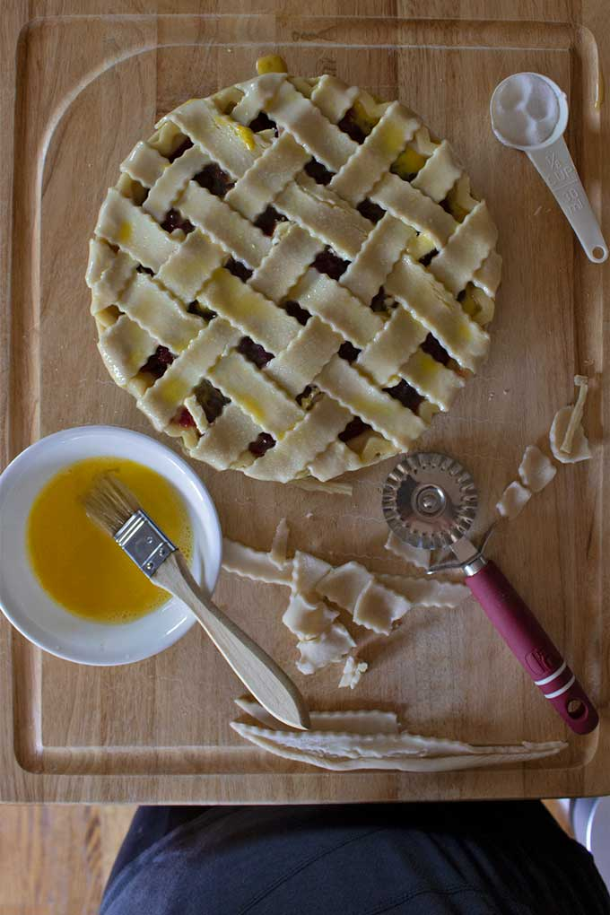 prepared homemade cherry pie on board with bowl of egg wash and extra pastry dough