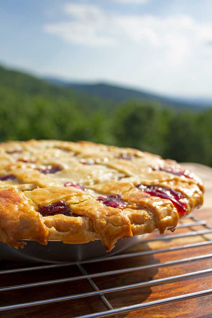 Easy homemade cherry pie made with fresh cherries bubbling in a thick rich filling inside a flaky buttery crust. A delicious summer all-American dessert!