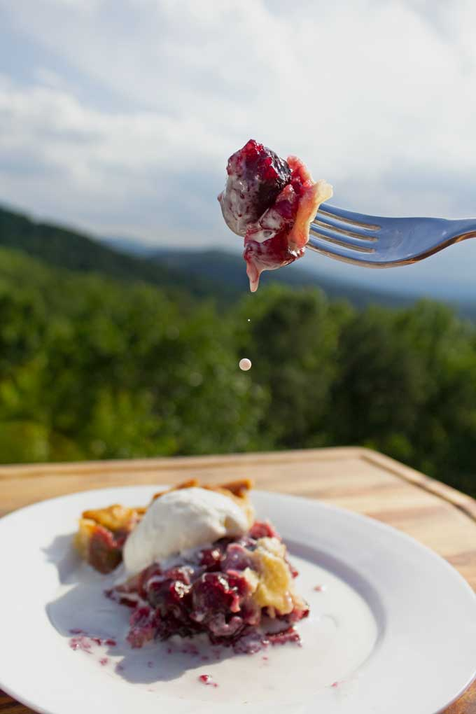 bite of homemade cherry pie on fork with dripping ice cream and mountain view