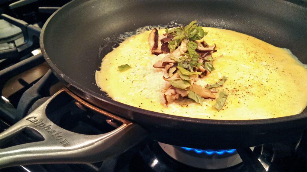 mushroom tomato basil omelet cooking in skillet
