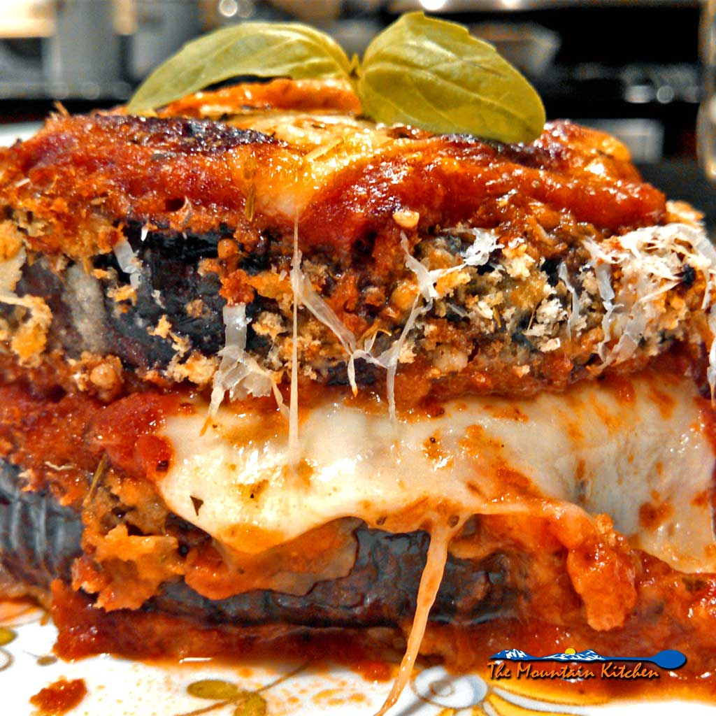 Healthy Oven-Baked Eggplant Parmesan ~ Delicate eggplant slices lightly breaded and oven-baked with tangy tomato sauce, layered with gooey browned cheese.