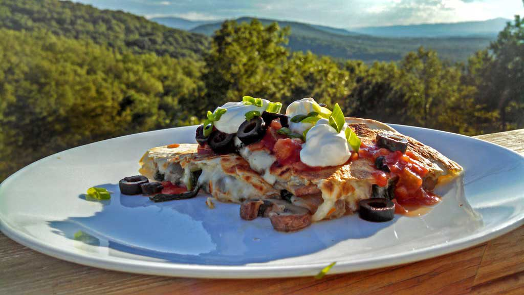Spicy Pepper Jack Mushroom-Spinach Quesadilla on plate with mountain view