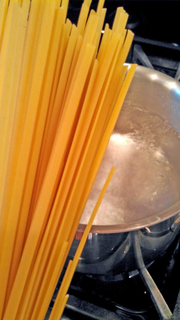 pasta getting ready to drop into boiling pot of water