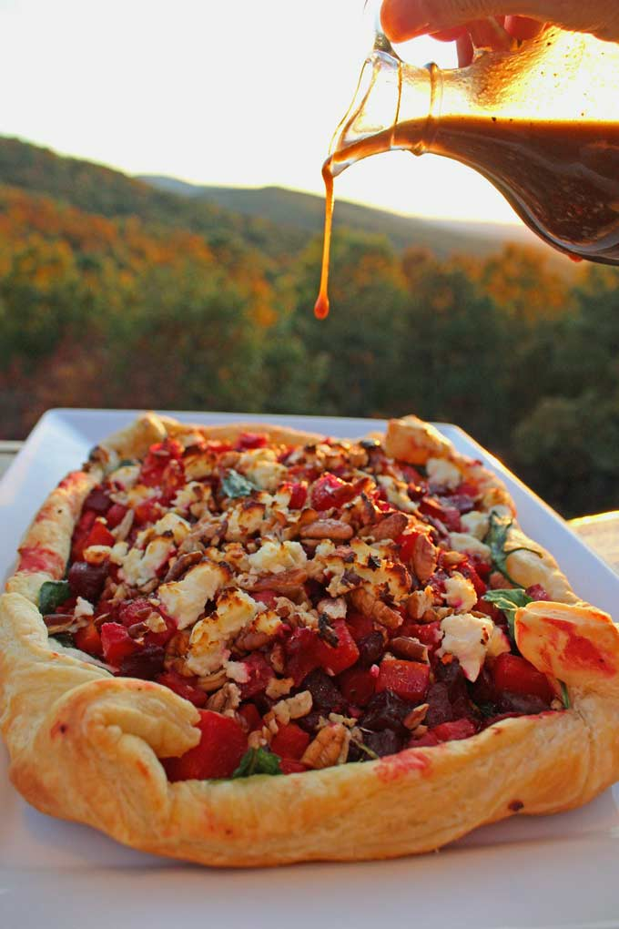 drizzling dressing onto the butternut squash and beet tart with mountain view