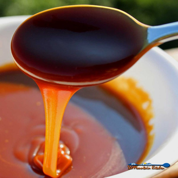 thick creamy caramel sauce oozing of spoon into bowl