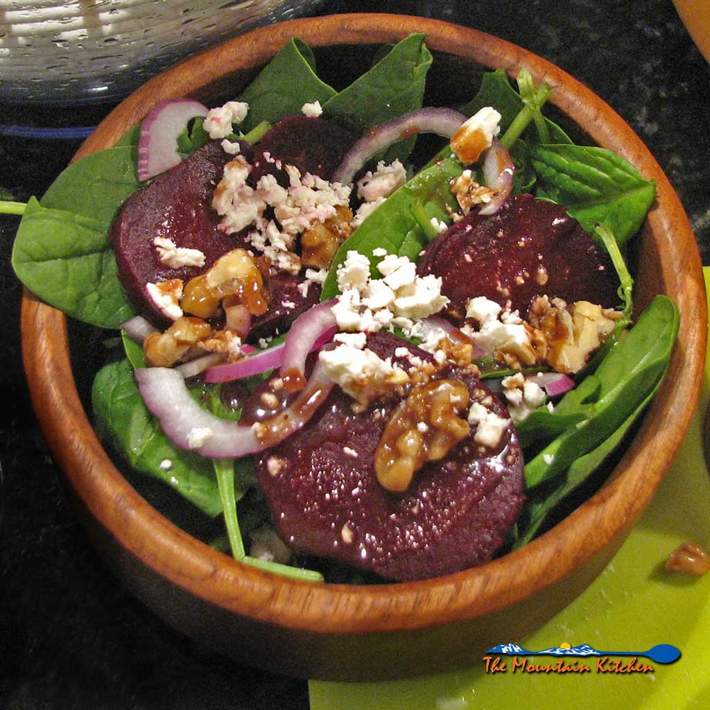 This roasted beet salad with fresh spinach, feta cheese, slices of red onion and candied walnuts, drizzled with balsamic maple cinnamon dressing.