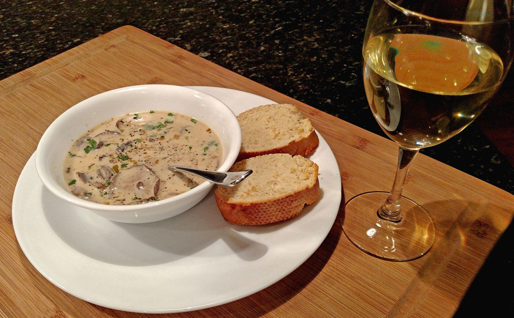 cream of mushroom soup in a bowl with bread and wine