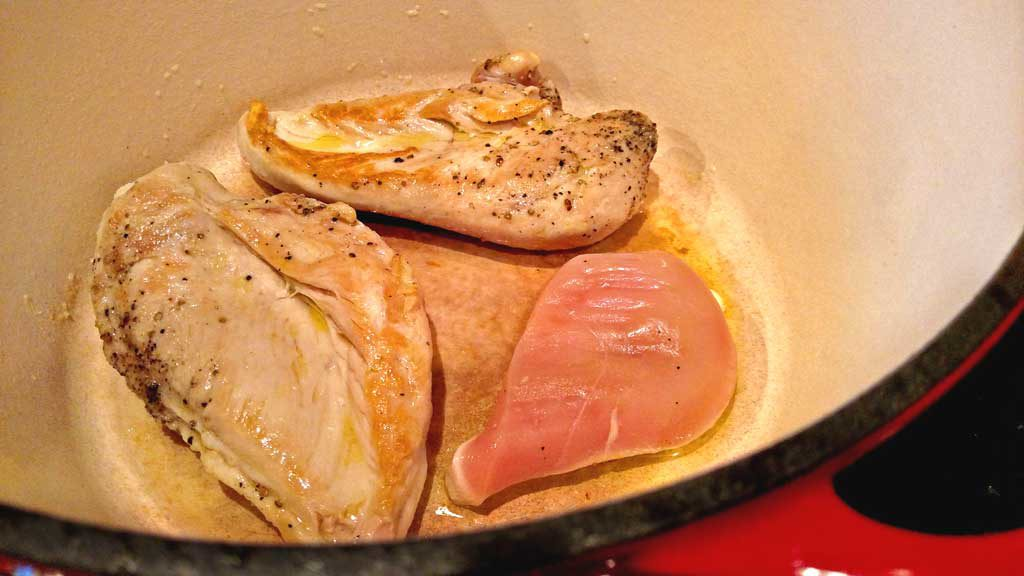 chicken breasts cooking in pot