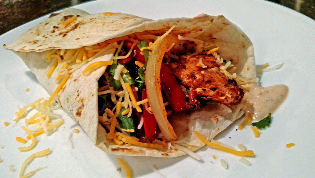 These easy weeknight chicken fajitas with seared chicken with Mexican spices served on a tortilla with chipotle sour cream, veggies, cheese and garnishes. TheMountainKitchen.com