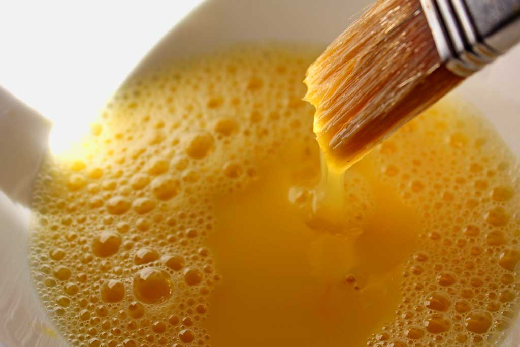 In the culinary arts, the term Egg Wash refers to a mixture of beaten eggs and some sort of liquid which is brushed pastry, before baking.   TheMountainKitchen.com