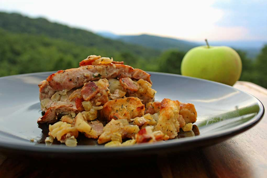 pork chops with apple-bacon stuffing on plate with an apple and mountain view