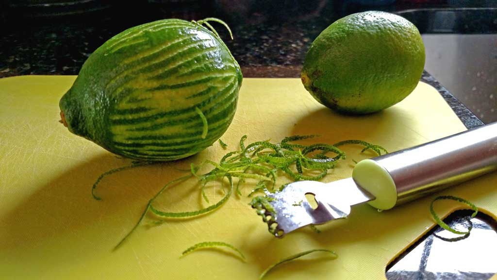 zested limes on cutting board with zester