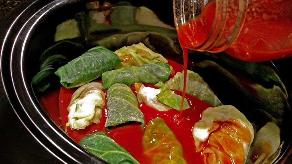 pouring sauce over frozen cabbage rolls in crock-pot
