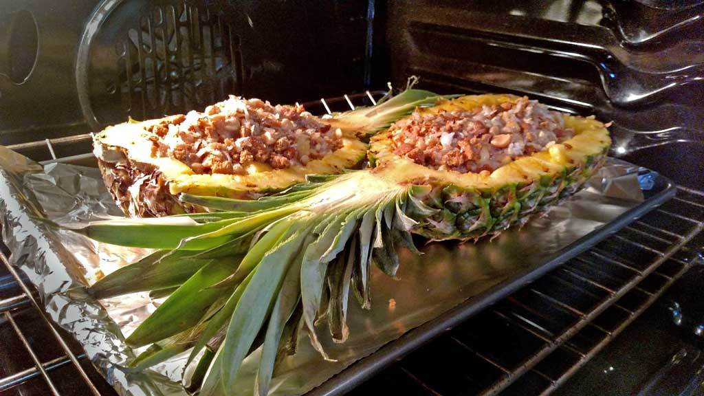 This stuffed pineapple is a tropical paradise,. Juicy pineapple baked and caramelized with a coconut, ginger snap topping. | TheMountainKitchen.com